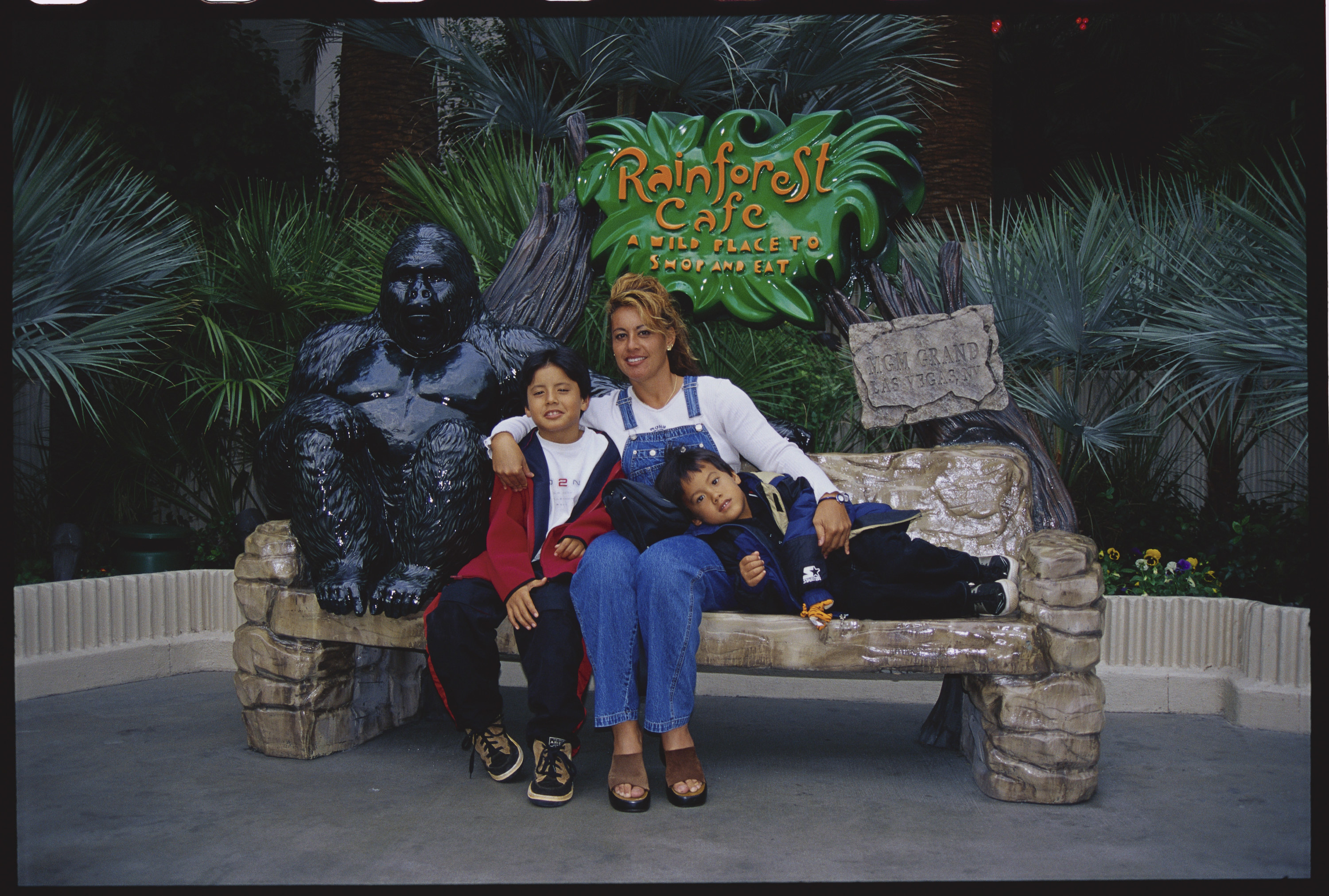 A mom with her two sons posing outside a Rainforest Cafe