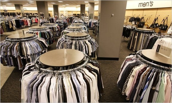 A photo of a old Nordstrom Rack with circular clothing racks in them