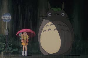 Satsuki, Mei, and Totoro wait at the bus stop in the rain