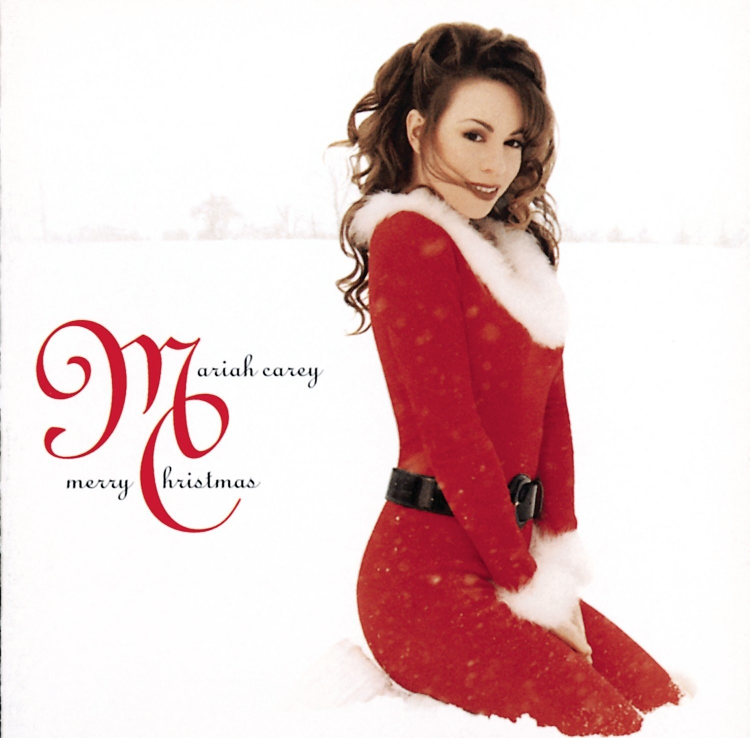 album cover of Merry Christmas showing Mariah Carey in a red jumpsuit lined with white fur kneeling in the snow