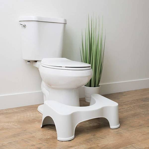 The Squatty Potty sitting on the floor in front of a toilet, like a stool