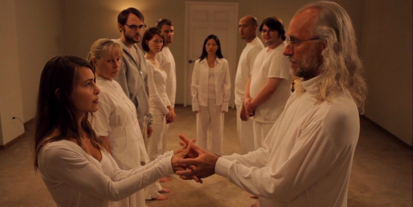 Brit Marling (Maggie) and Richard Wharton (Klaus) holding hands in front of a group of seven cult members in 'Sound of My Voice'
