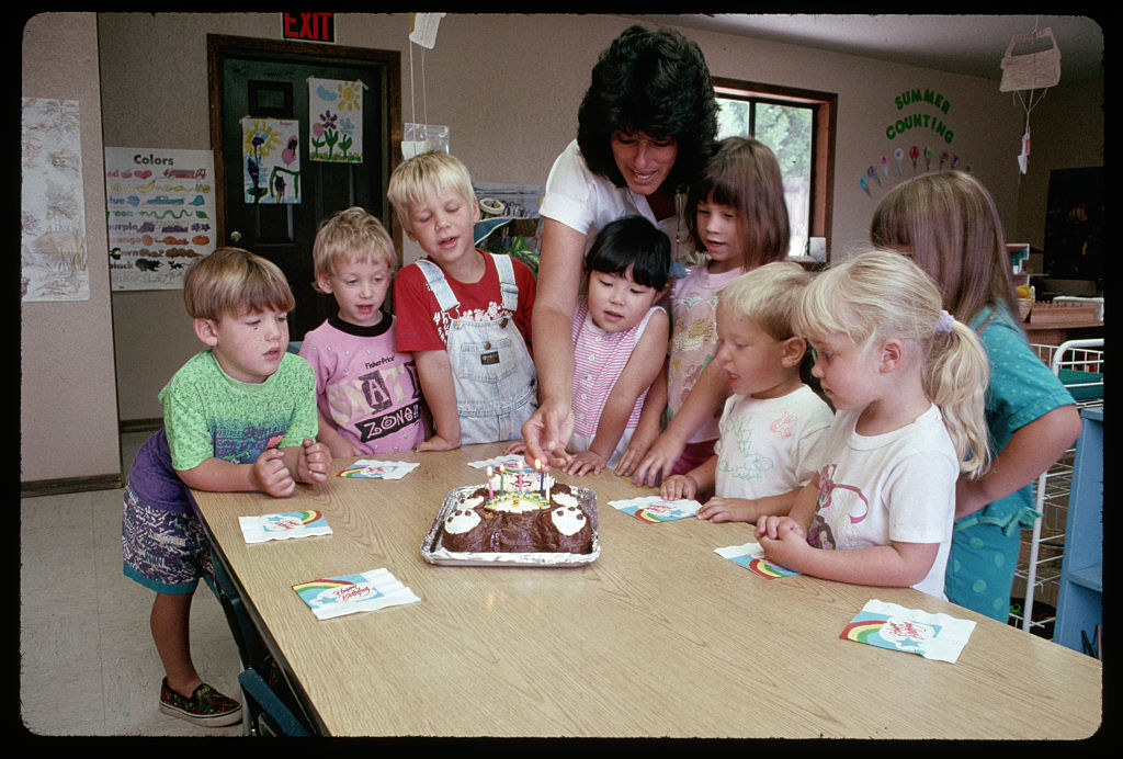 Preschoolers watching a birthday cake being lit by the teacher in the early '90s