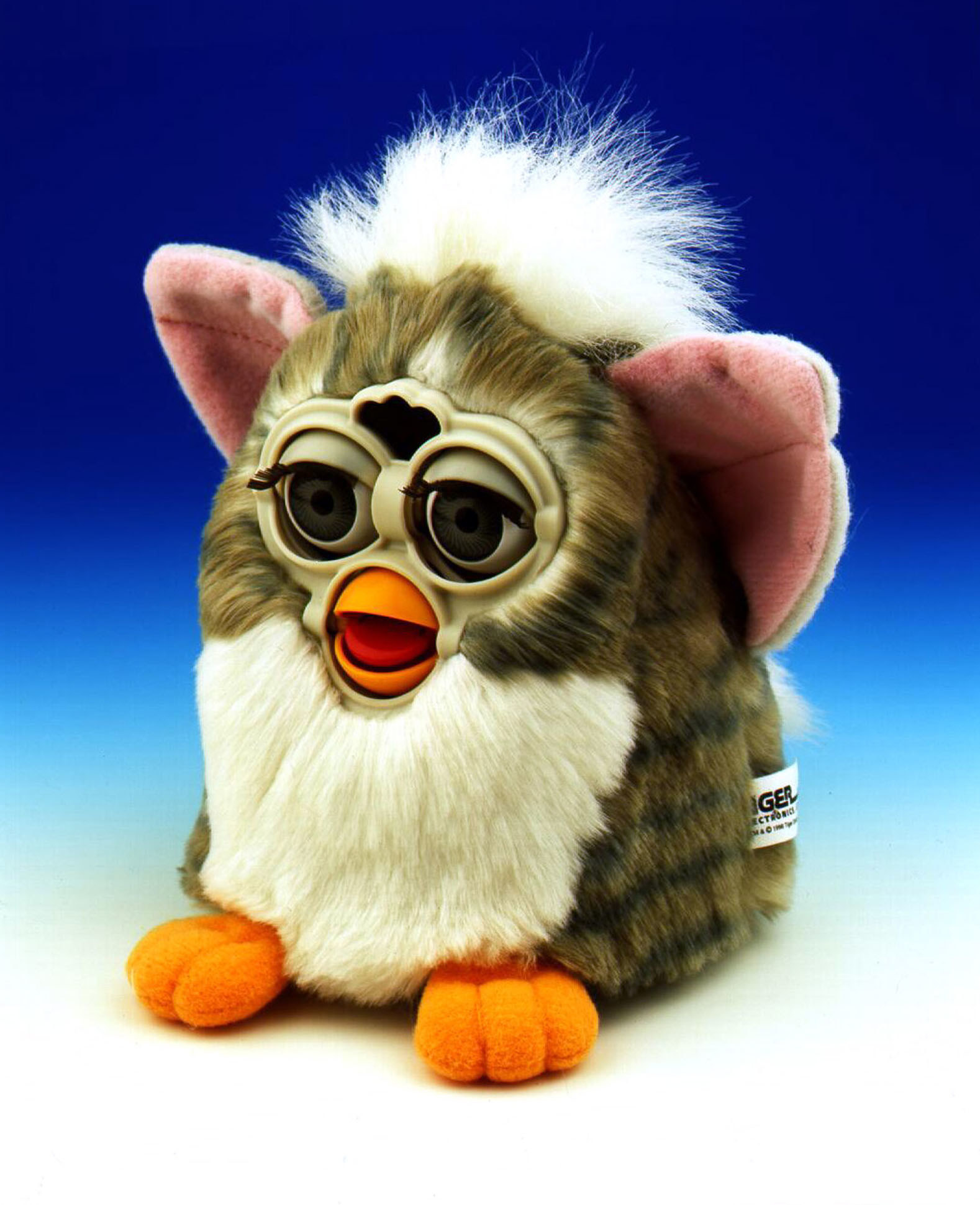 A promotional product photo of a brown and white Furby
