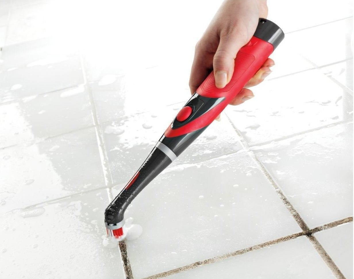 Red and black scrubber cleaning grout