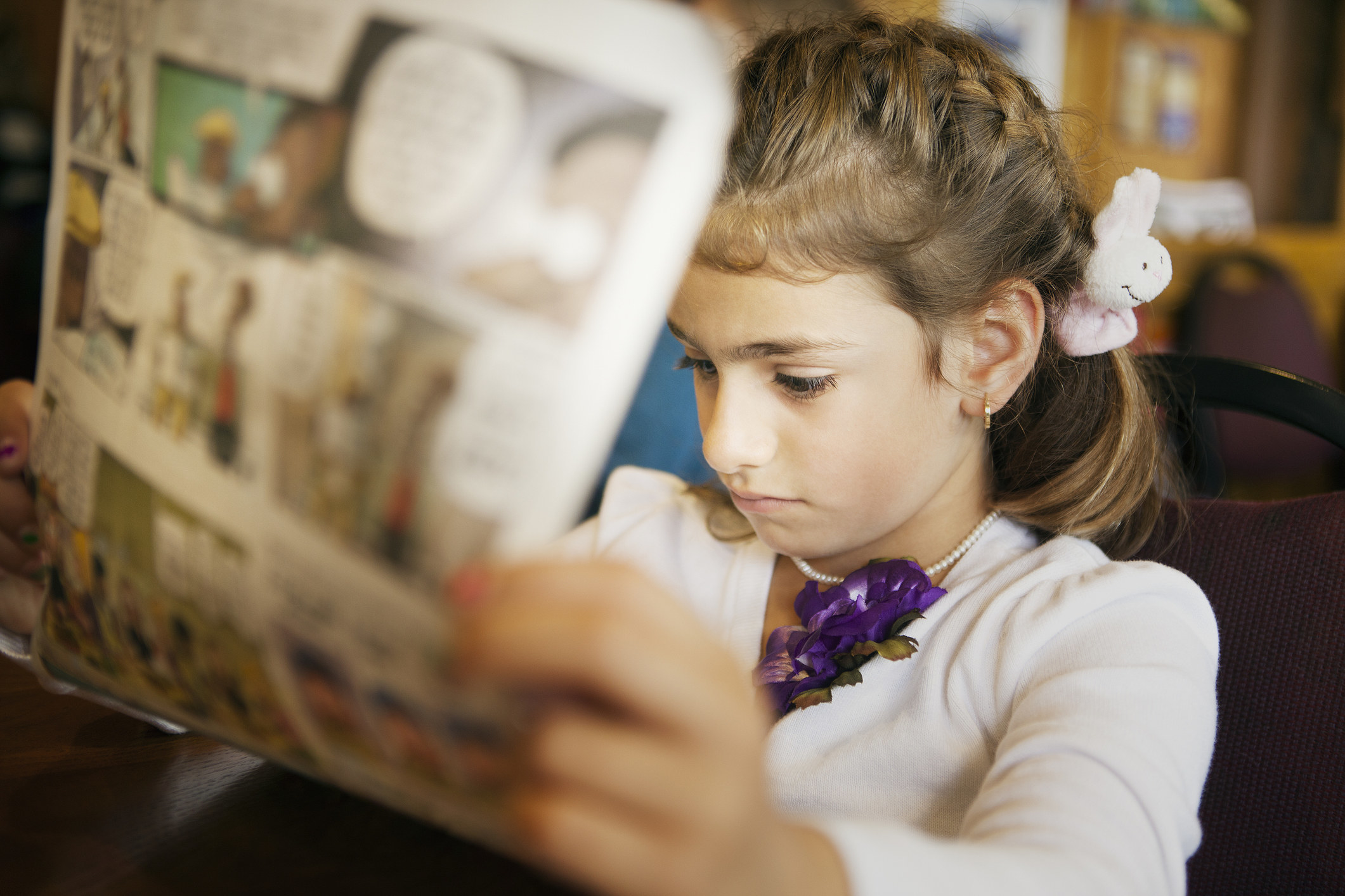 A stock image of a little girl reading the Sunday comics