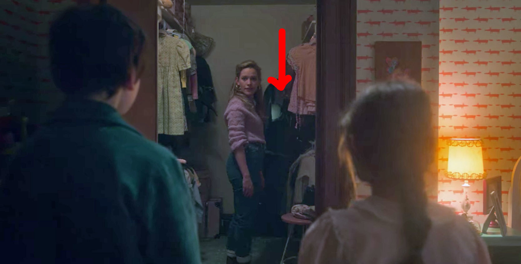 Miles and Flora stand facing Dani, who is in the closet in front of a mirror; a red arrow points to a shape in the mirror