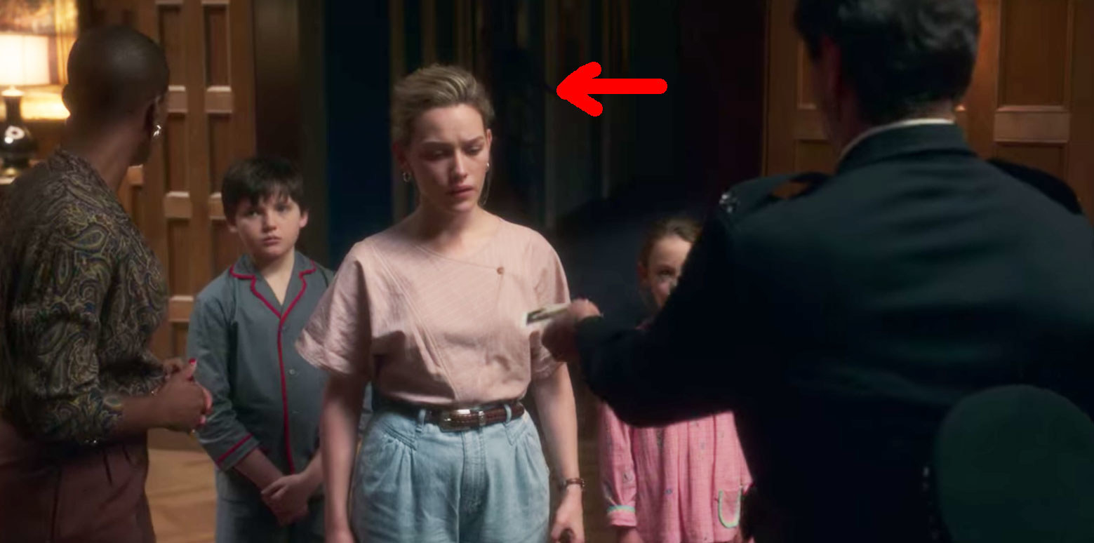 A policeman stands facing Dani, Hannah, Miles and Flora in the foyer; a red arrow points to the shape of the plague doctor behind them