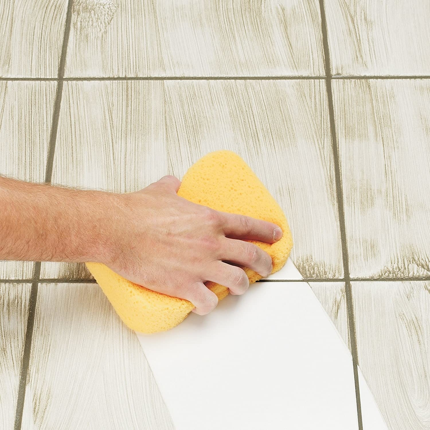 A person scrubbing their tiles with the grout sponge