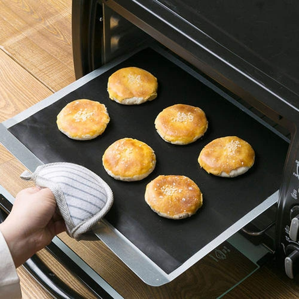 A person pulling a sheet of buns out of a toaster oven, the sheet is lined with a grill mat