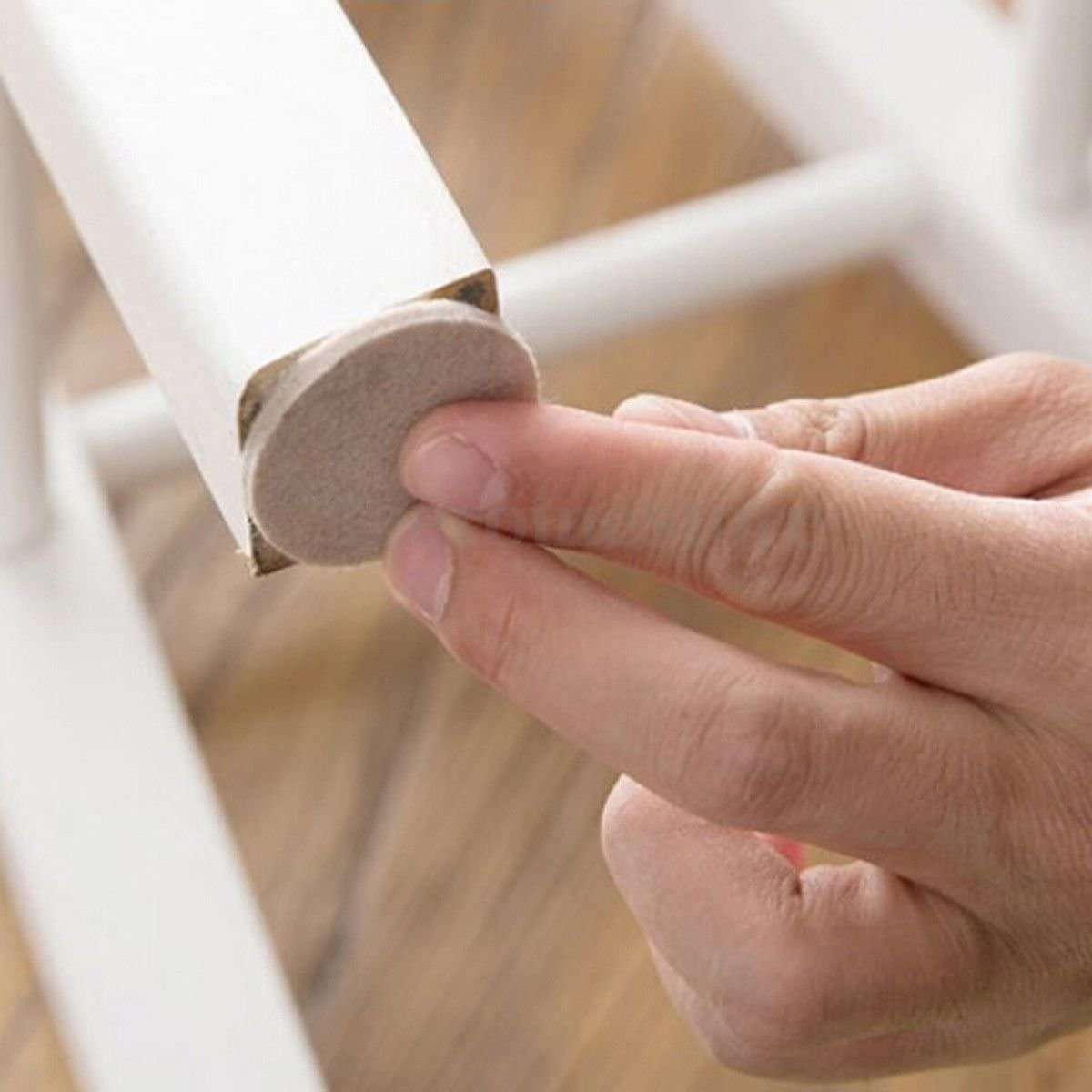 A person sticking a felt pad onto the bottom of a chair leg