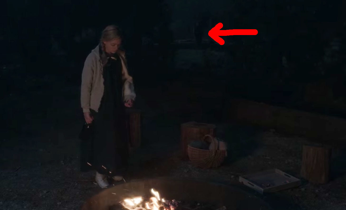 Dani stands in front of a fire outside at night; in the dark background a red arrow points to a shadowy figure