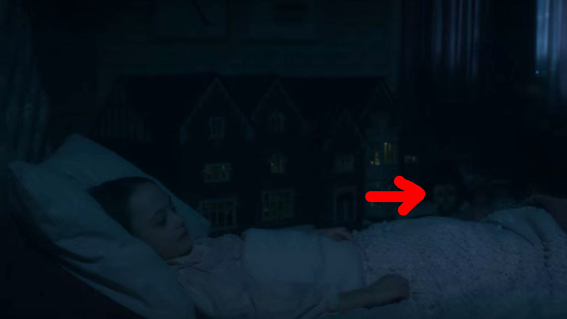 Flora lies in bed; in the background a red arrow points to the little boy ghost wearing a doll face