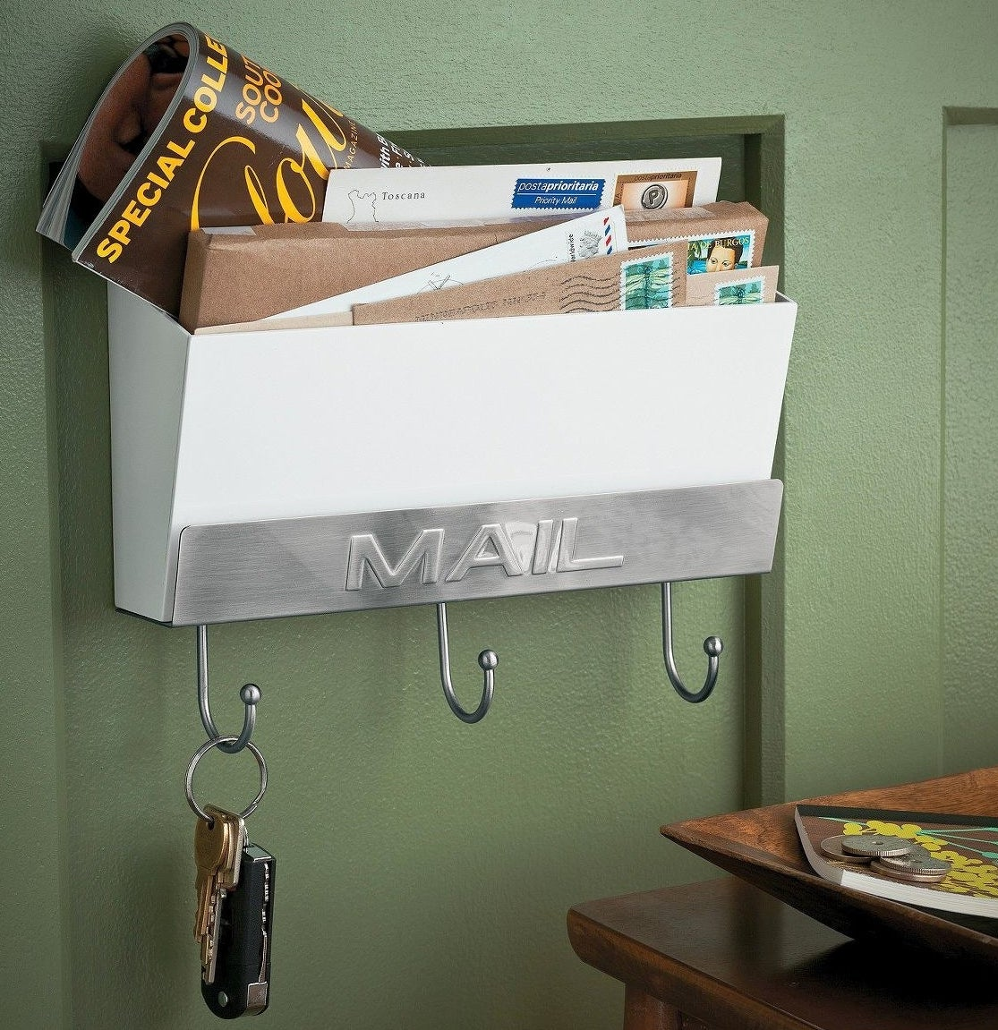 White mail holder with silver accents and three hooks underneath