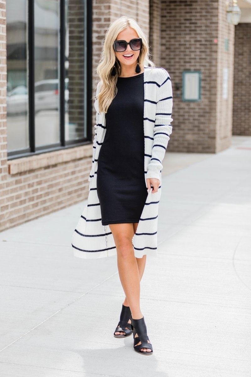model wears white cardigan with black stripes