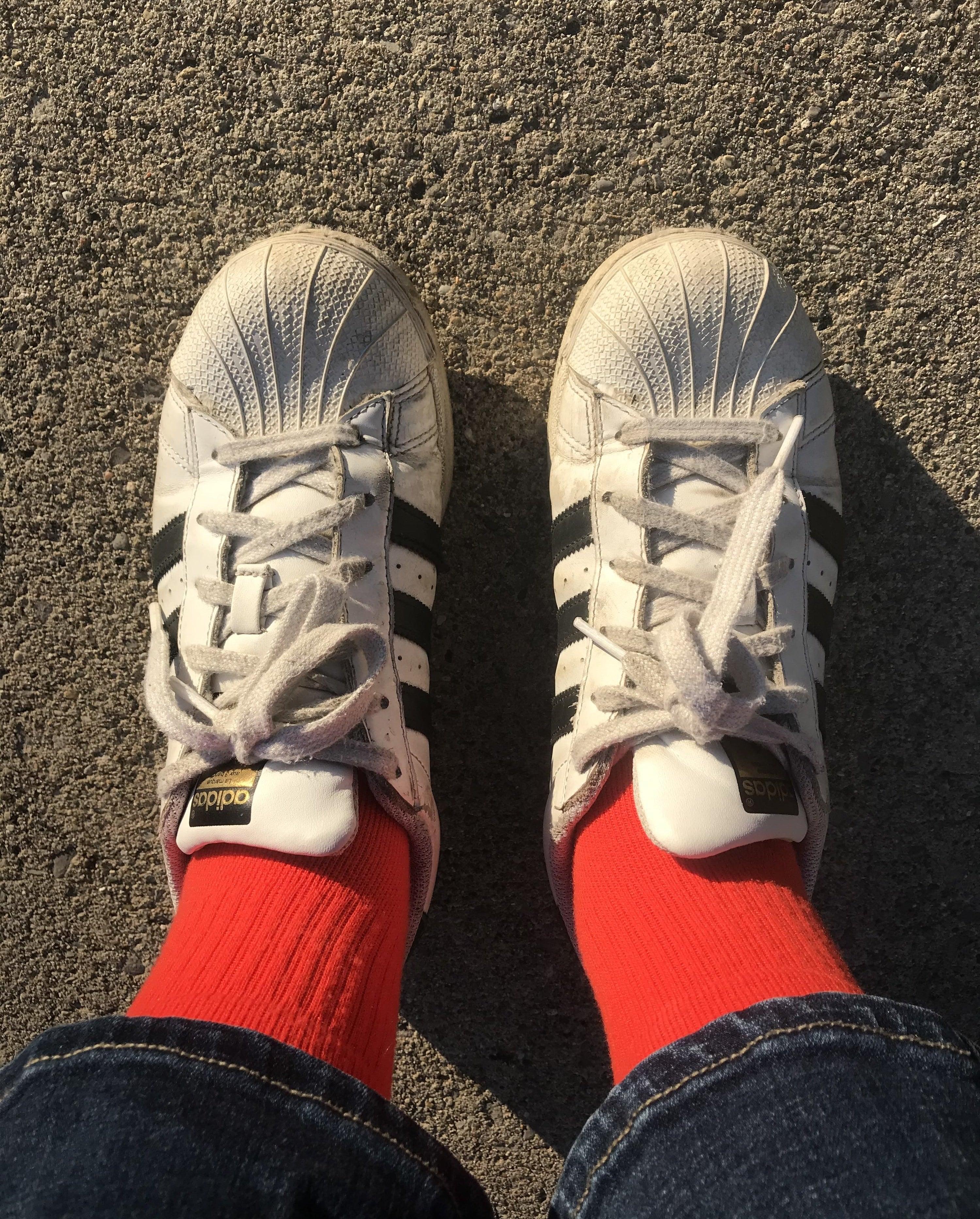 writer wearing worn black and white adidas sneakers