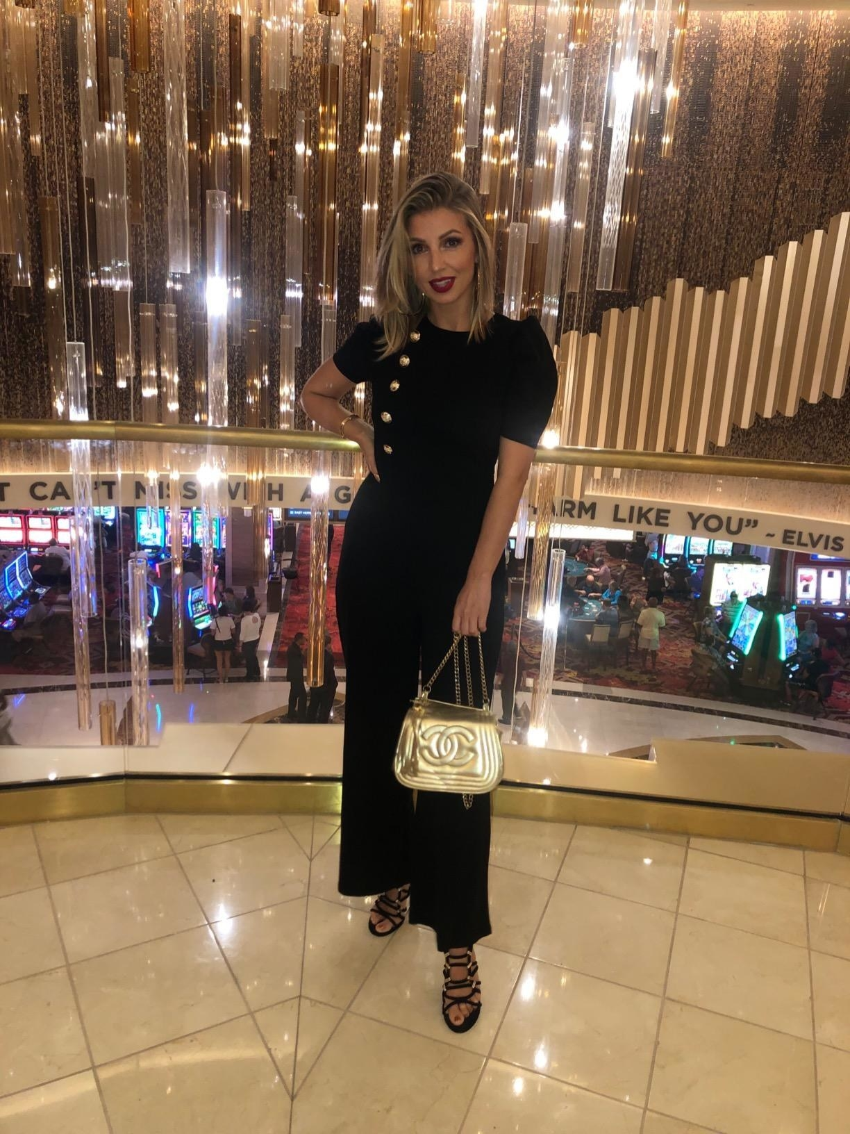 A reviewer wearing the short puff-sleeve jumpsuit with gold buttons on the right side of the chest in black