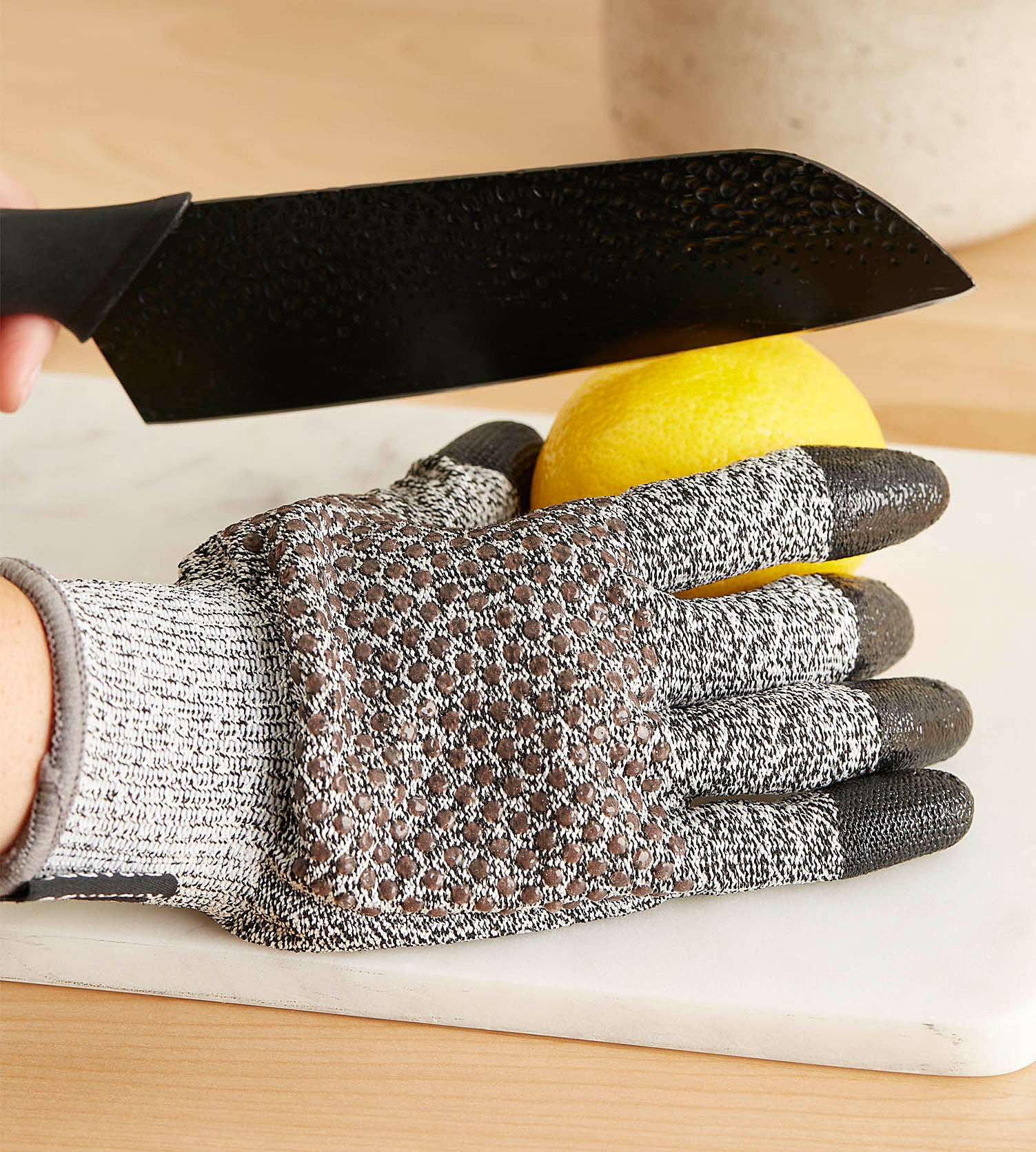 A person wearing the glove and cutting a lemon