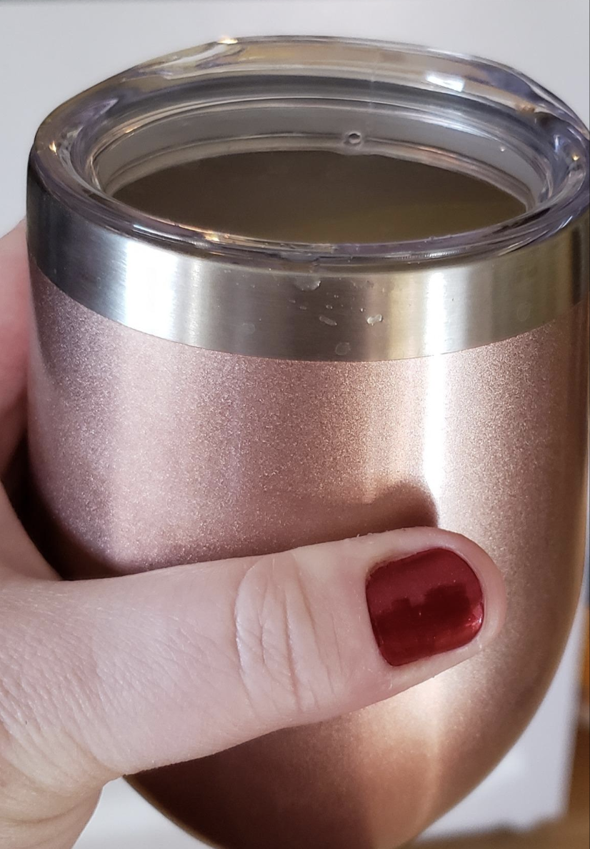 A reviewer holding the white tumbler