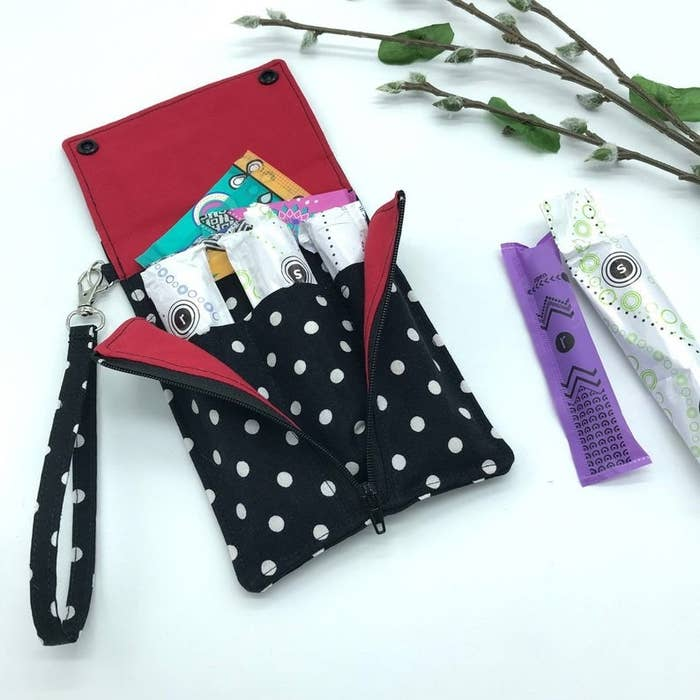 A black, polka-dotted tampon pouch storing three tampons and a few panty liners