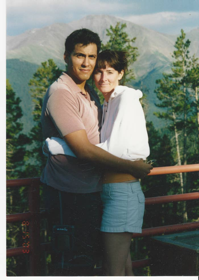 Rey River and his wife, Allison, stand outside in front of a gate by trees and a mountain