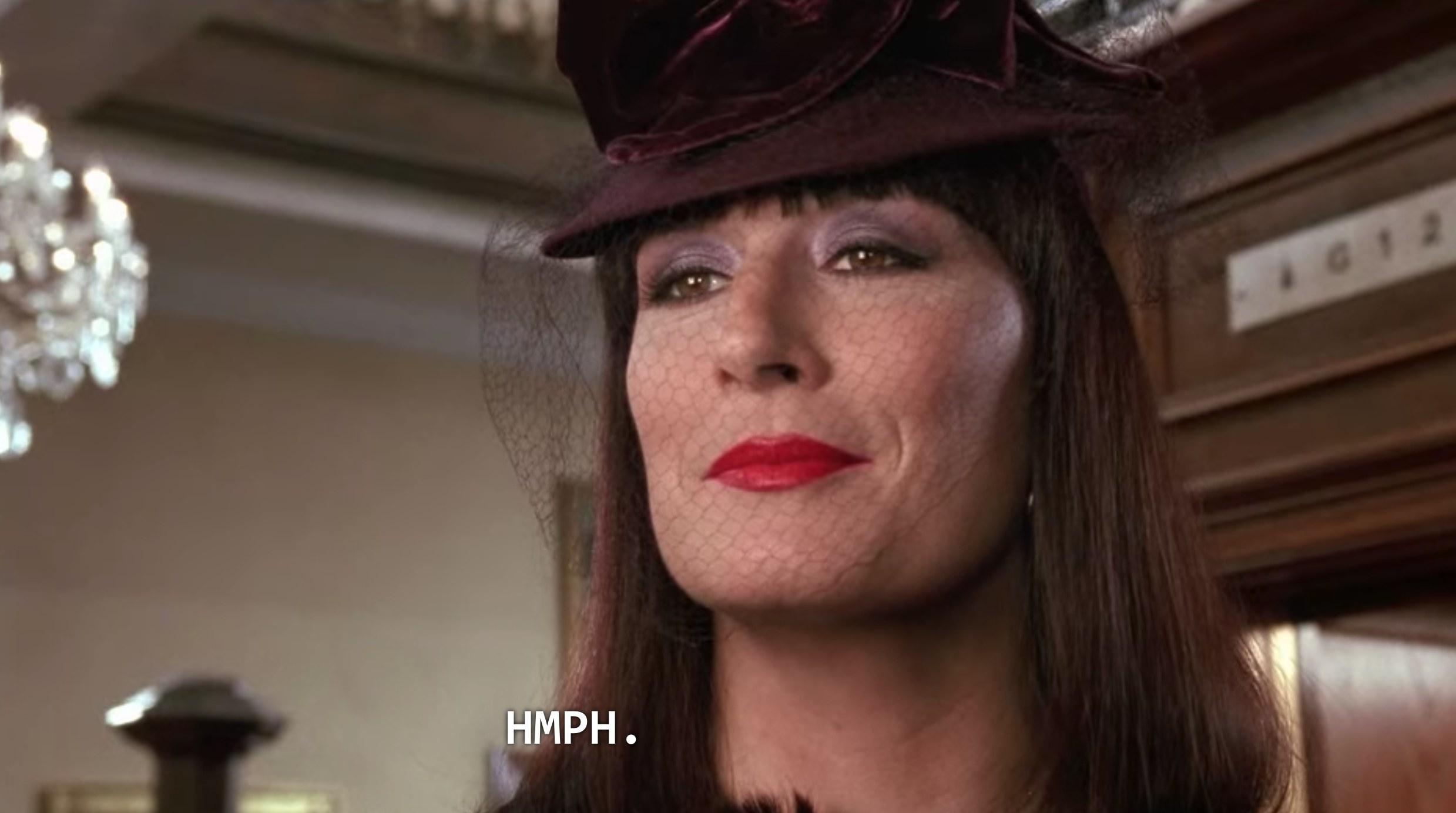 Anjelica Huston with a dark purple hat