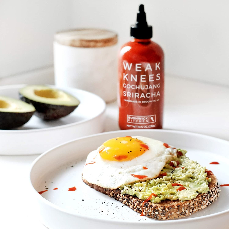 Avocado toast topped with a fried egg and Bushwick Kitchen's Weak Knees Goghujang Sriracha sauce.
