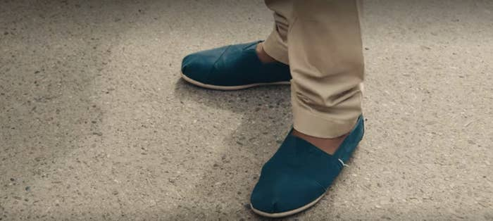 A still image of a man's feet wearing Toms-brand shoes
