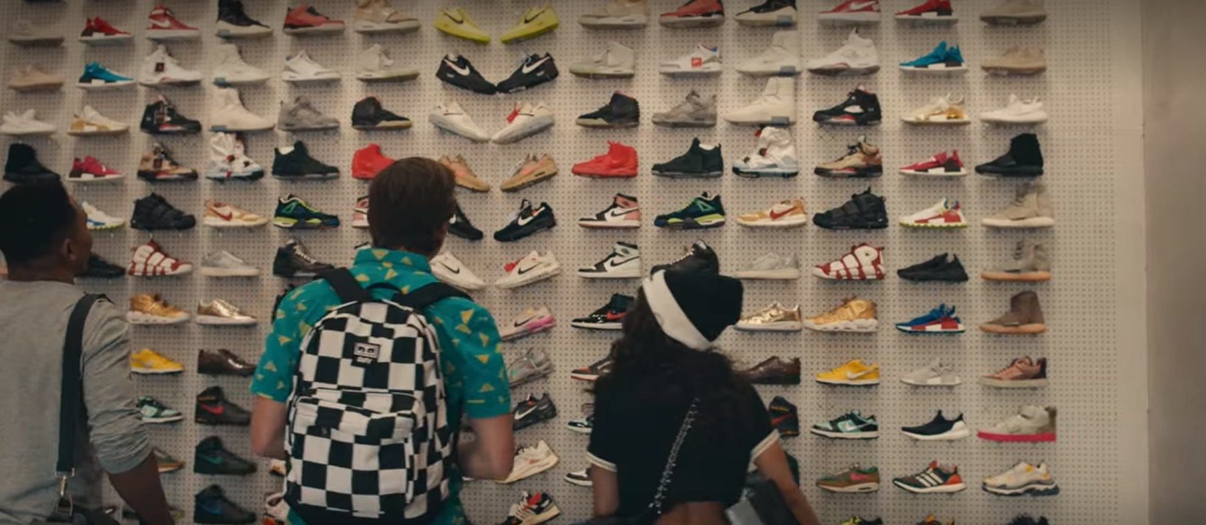 A still image of three people with their backs to the camera standing in front of a wall of sneakers.