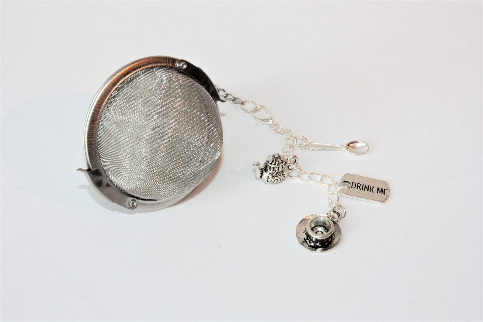 "Silver tea diffuser with clip on charms of a teapot, teacup, teaspoon, and the words ""drink me"""