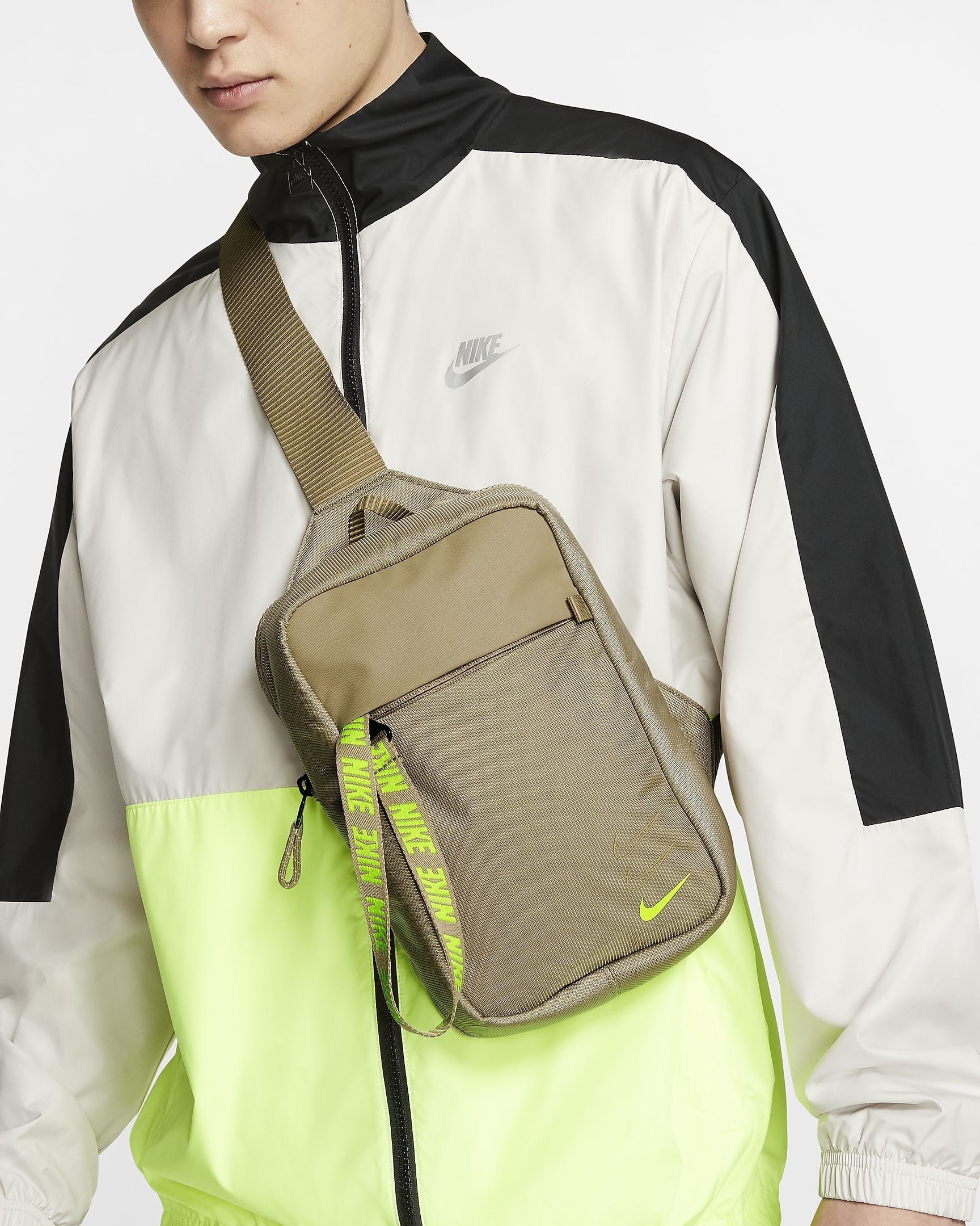 Model wears Nike green hip pack over neon green and white zip-up jacket