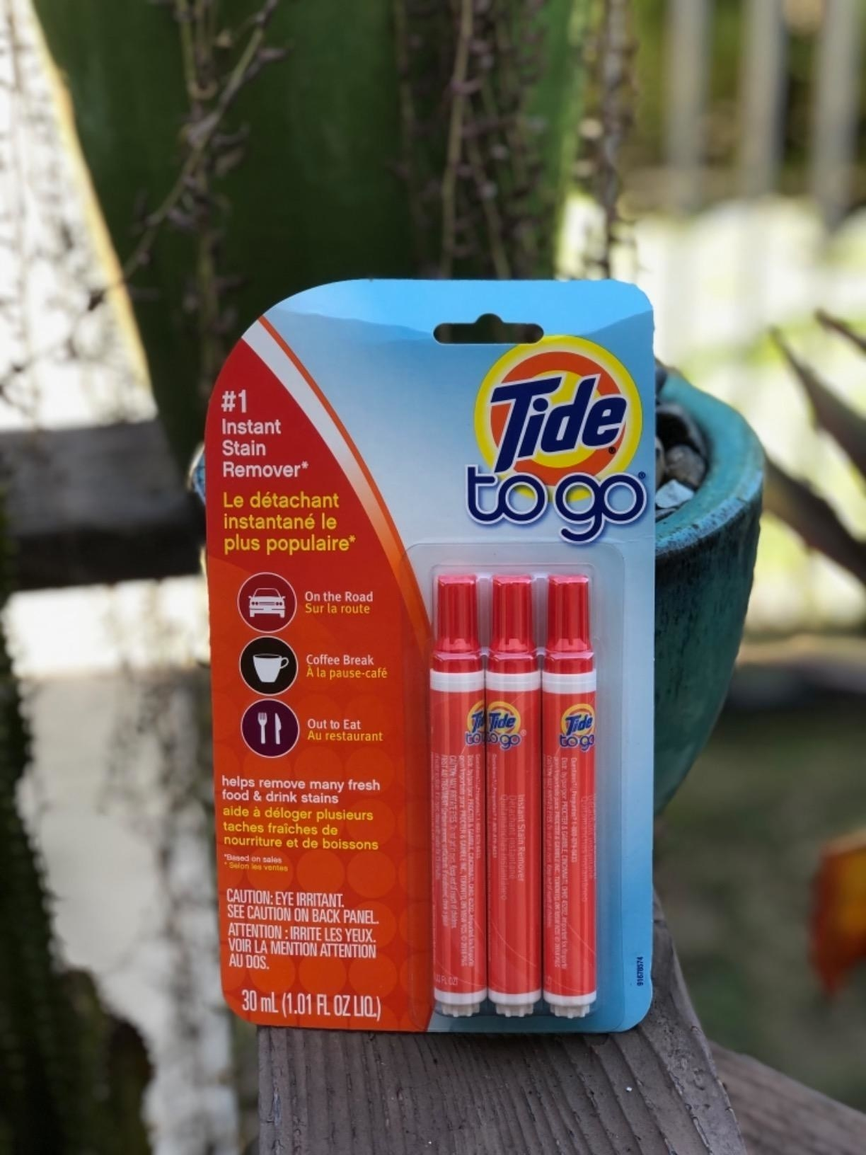 A customer props a pack of three tide stain remover pens on a wooden shelf