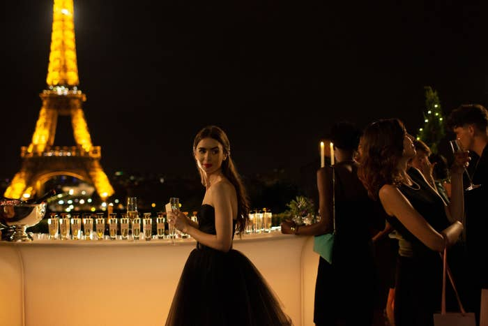 Emily standing at a rooftop party with the Eiffel Tower in the background.