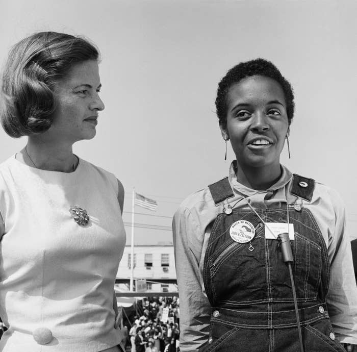 A Black woman, wearing a March on Washington pin, and a white woman stand side by side