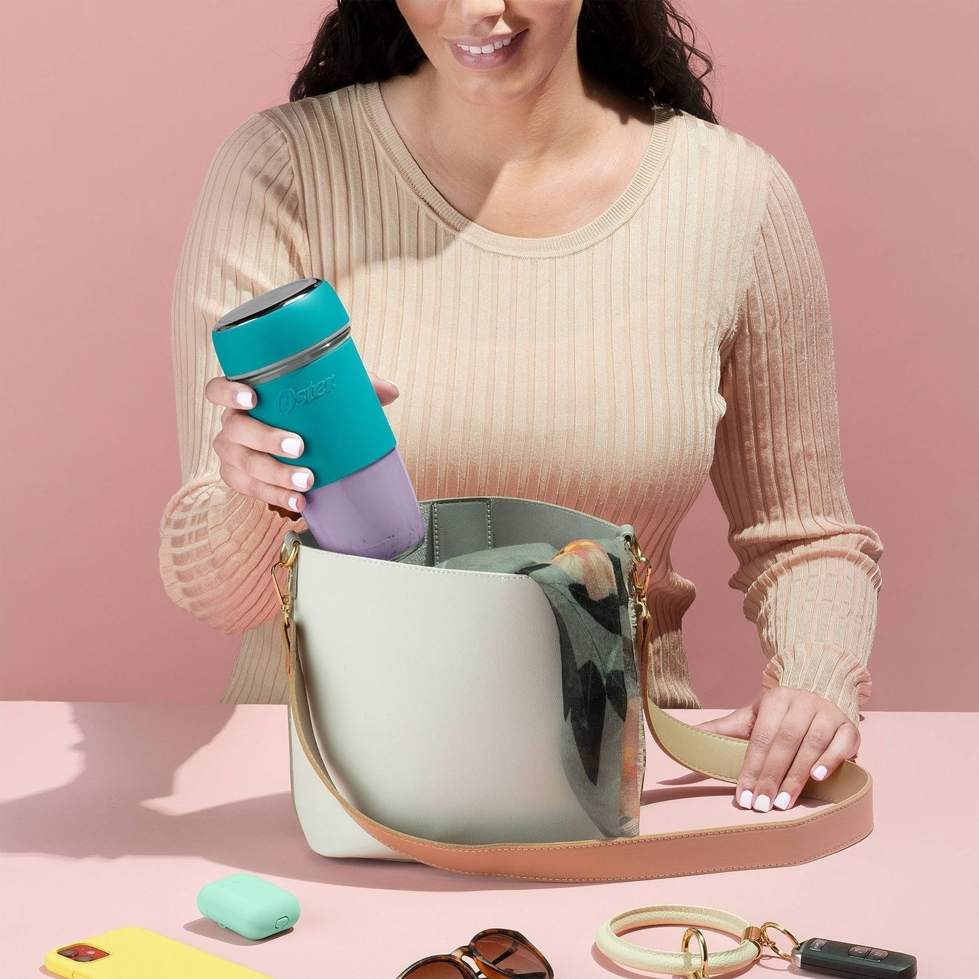 Model holding the teal portable rechargeable blender