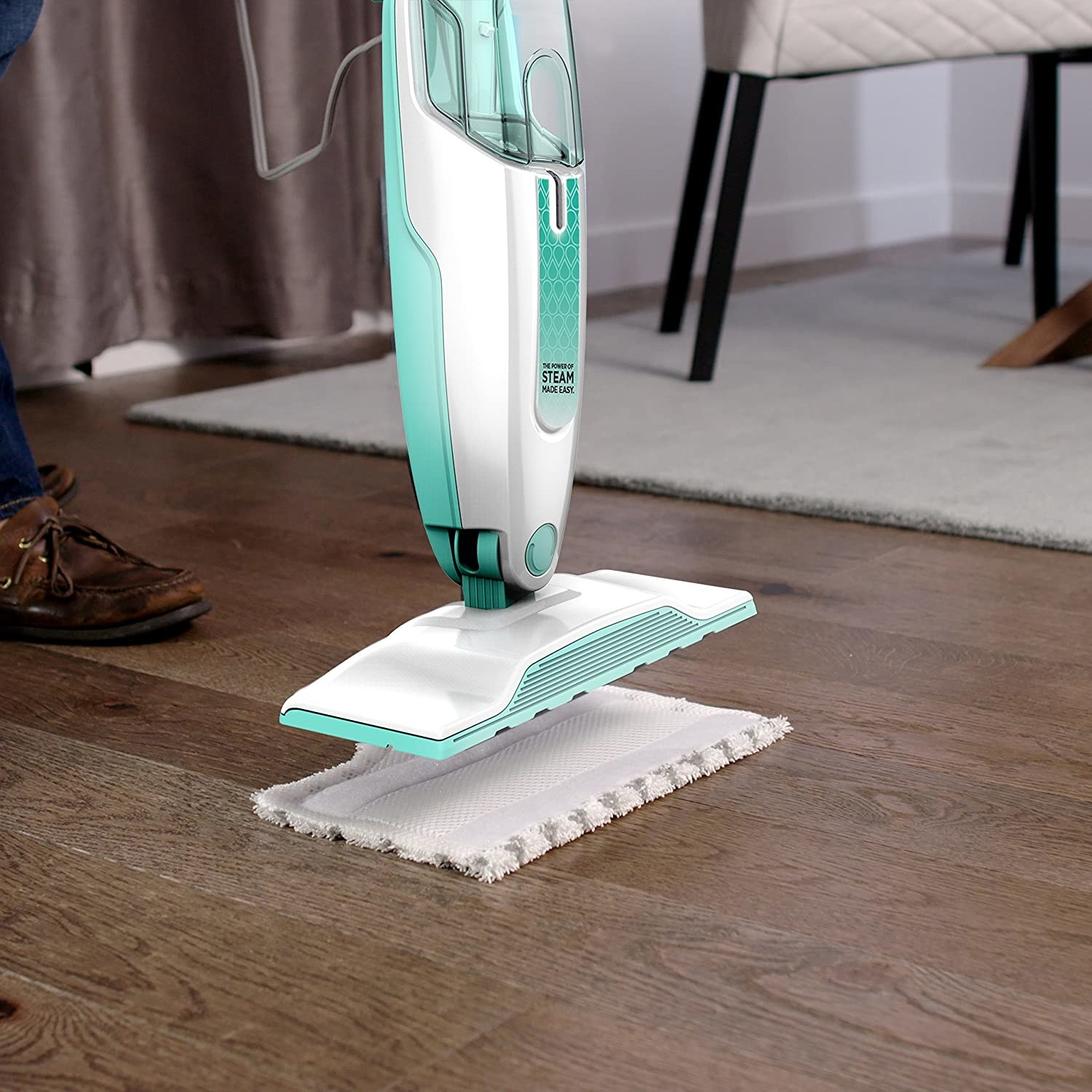 A steam mop above a steam mop pad on a hardwood floors
