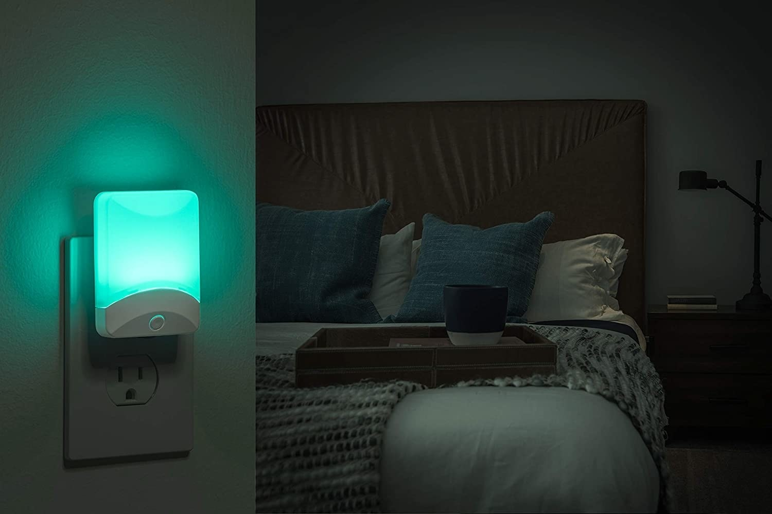 The nightlight plugged into a bedroom wall in front of a bed