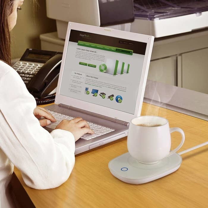 This desk mug warmer pictured with a mug next to a woman working on her laptop.