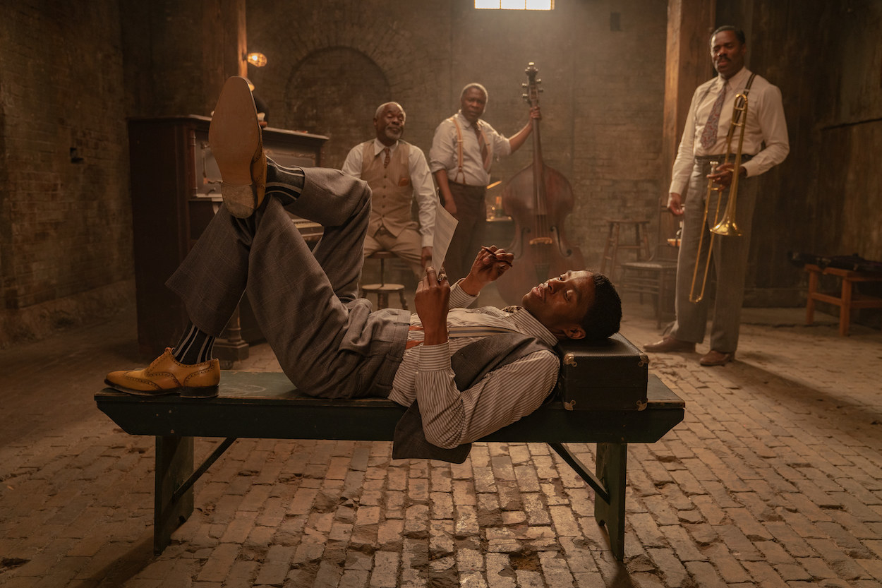 Chadwick lying on a bench in a basement while men with instruments stand in the background