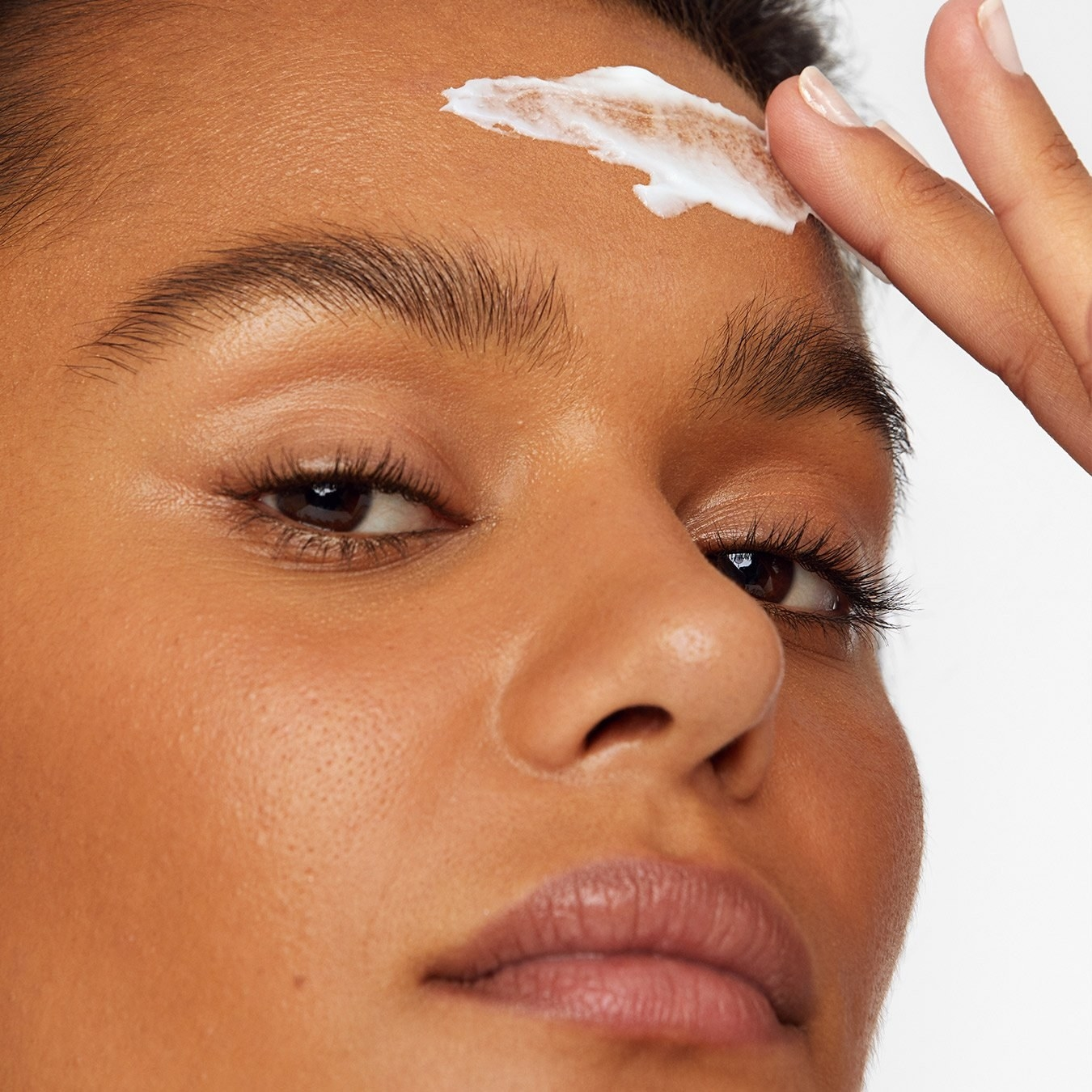 A model applying the white cream to their forehead