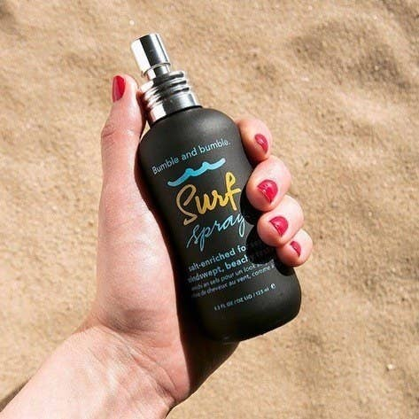 A hand holding a bottle of the spray on the sand
