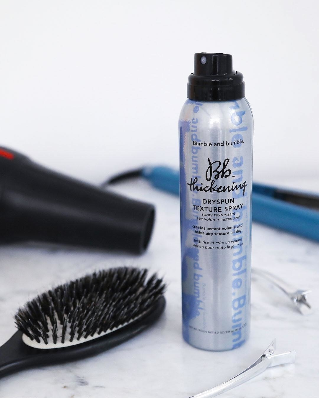 A bottle of the product beside a hair brush