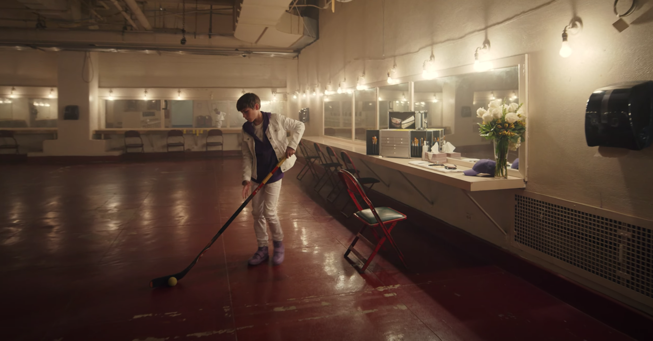 Jacob guides a ball with a hockey stick during the music video