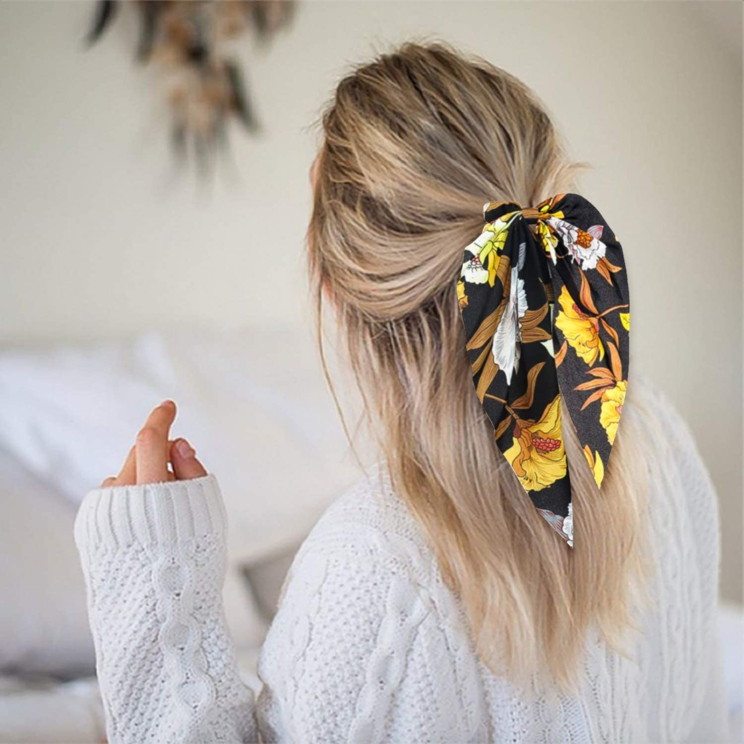 A person with a bow scrunchie in their hair
