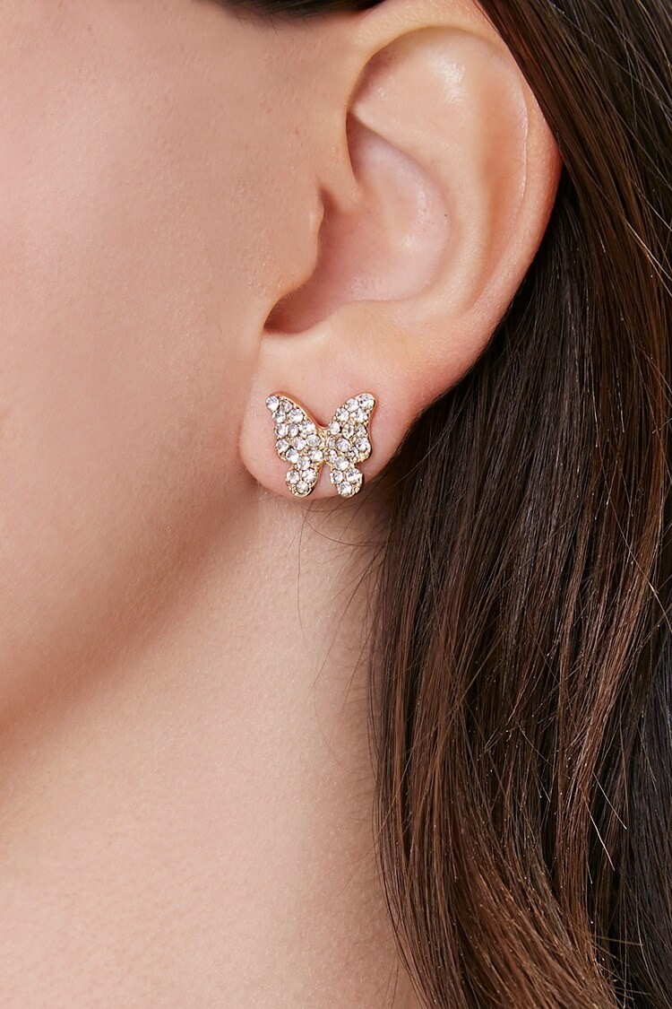 model ear wearing a butterfly stud earring which is gold and has rhinestones on it
