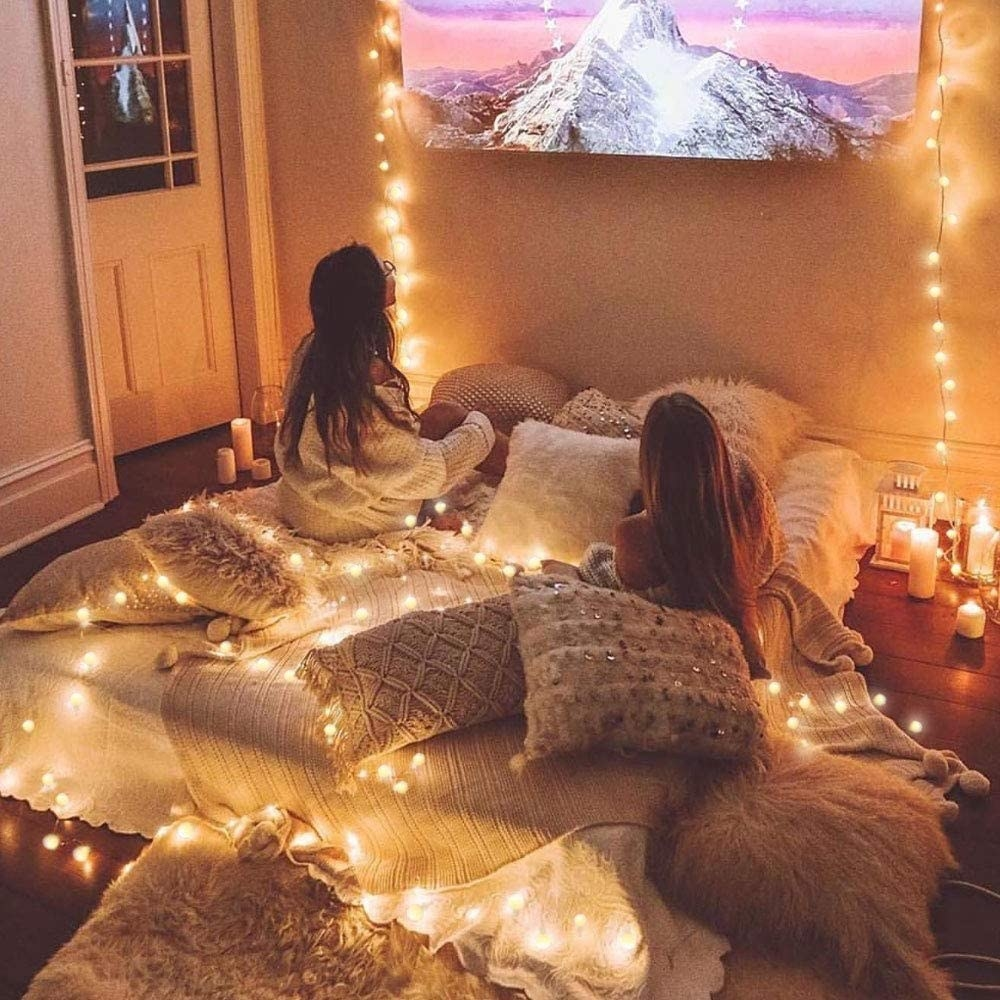 two people laying on a mattress watching a movie with globe string lights draped around them