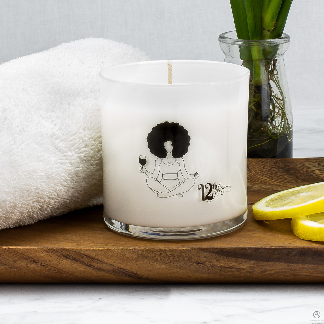 The white candle with an illustration of someone sitting crosslegged holding a glass of wine on the front