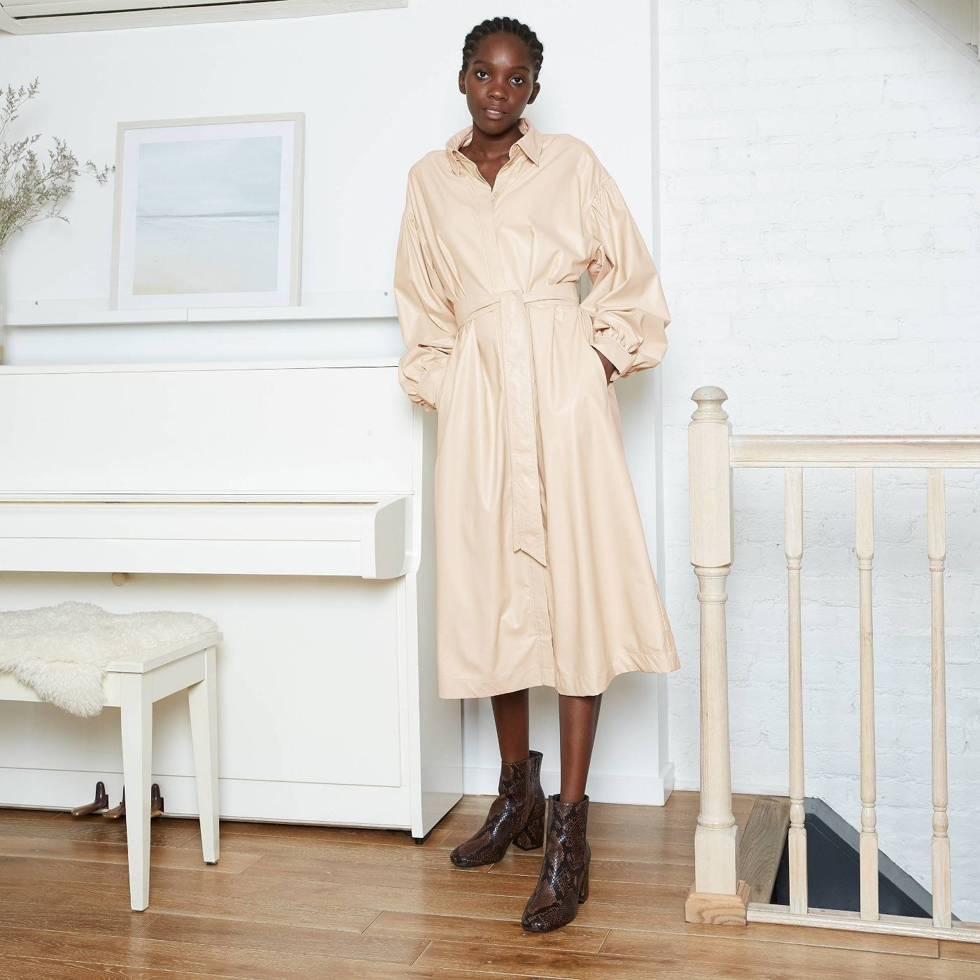 Model wearing the cream midi dress with brown snake-print boots