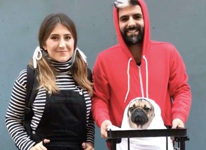 A woman and man hold their pug as they are all dressed like characters from E.T.