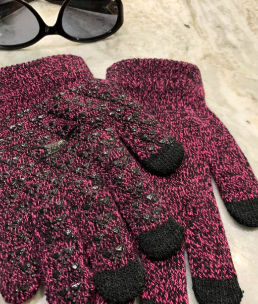 reviewer photo of smartphone gloves in pink laying next to a pair of sunglasses